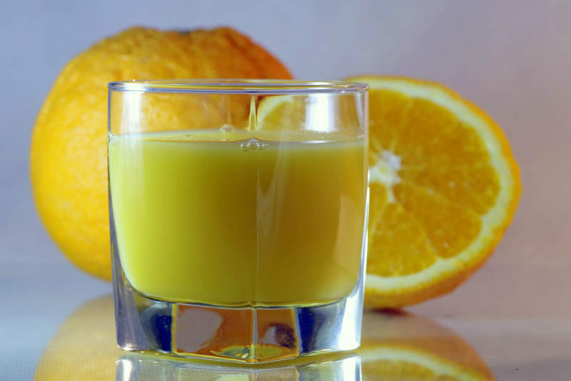 oranges behind glass of juice