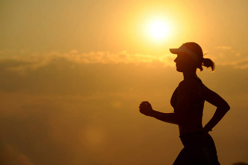 woman running silhouette sunset